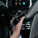 Imagen de mano de persona con movil dentro de un auto